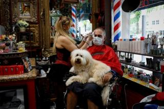 At a barber shop, a hairdresser cuts the hair of a man with a dog on his lap