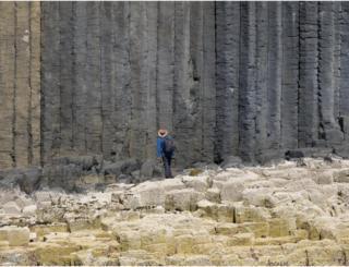 Man looking at Staffa's columns