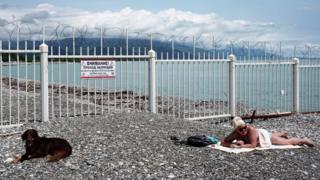 Uma mulher e um cachorro tomam banho de sol na fronteira entre Abecásia e Rússia, um dos poucos países que reconhece formalmente a região como país