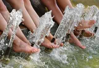 Tourists refresh their feet in a pool during a heatwave in Montpellier
