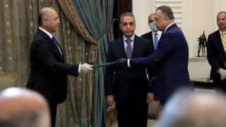 President Barham Saleh (L) and Mostafa al- (R) wore gloves at the ceremony