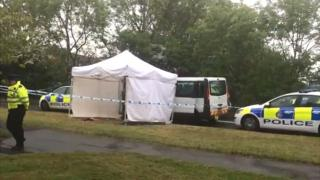 A white tent and police tape next to a taxi