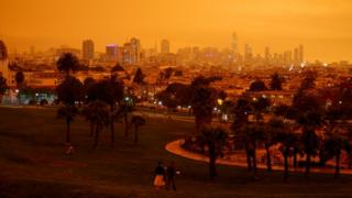 weather Downtown San Francisco is seen from Dolores Park under an orange sky