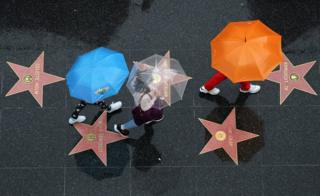People walk on the Hollywood Walk of Fame in the rain in Hollywood, Los Angeles, California, U.S.