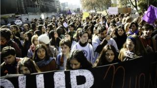 Schoolchildren can be seen taking part in a march against sexism in Santiago