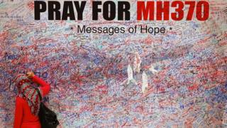 A woman leaves a message of support and hope for the passengers of the missing Malaysia Airlines MH370 in central Kuala Lumpur (16 March 2014)