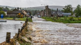 Water rushes over the road out of Dallas in Moray