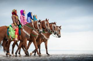 Women from the Oman Royal Cavalry's Combined Bands who are performing at The Royal Edinburgh Military Tattoo exercise their horses on the city's Portobello beach., 16 August 2018.