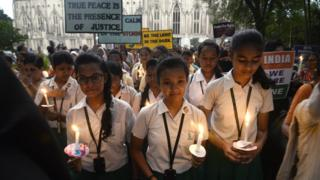 School girls hold candles and placards during the march against rape