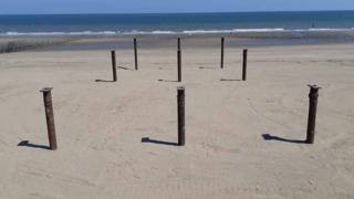 Pier struts stick out from the sand on Colwyn Bay beach