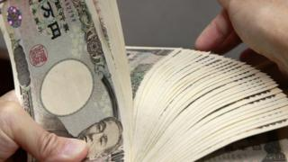 A bank teller counting 10,000 yen bank notes in Tokyo