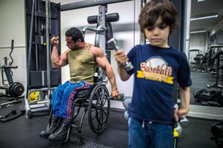 A man lifts weights in a gym while a small child lifts another one.
