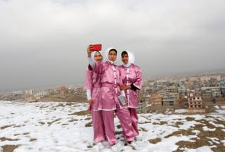 Latifa Safay (right), Hanifa Doosti (centre) and Suraya Rezai (left), students of the Shaolin Wushu club, take a selfie before practicing on a hilltop in Kabul, Afghanistan