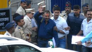 Indian Bollywood actor Sanjay Dutt (C) waves as he is escorted by officials from Yerwada Jail in Pune on February 25, 2016.