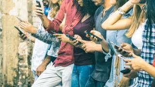 Pessoas com celulares em mãos