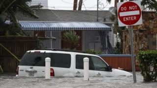 Una camioneta en mitad de una calle inundada.
