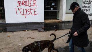 "Man walks past graffiti which reads: ""Burn the Elysée"""