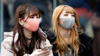 Two young women wear face masks in the street in Tokyo, in tones of pink and light grey