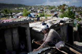 A man fixes the roof of a house affected by Hurricane Matthew in Jeremie, Haiti