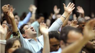 People attend a mass in evangelical church in Goiania, Goias State, Brazil, on May 19, 2013.
