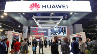 Attendees pass by a Huawei booth during the 2019 CES in Las Vegas