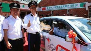 Two Chinese police officers smile alongside a Zambian colleague sitting in a police vehicle