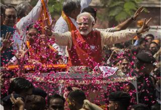 Supporters throw flower petals as Narendra Modi rides in an open jeep in Vadodra