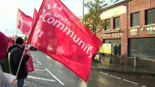 A protester waves a Unite trade union flag outside a Sinn Féin office on Belfast's Falls Road