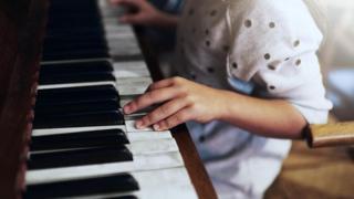 Дівчина грає на фортепіано