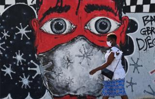 A woman wearing a mask walks past a large mural depicting a person wearing a mask.