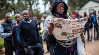 A man reads a newspaper with the headline 'Great day for Kenya' while waiting to cast their ballot in the general elections at a polling station in Kilimani Primary School, Nairobi, Kenya, on August 8, 2017 during the nationwide elections