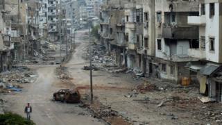 Burnt car and damaged buildings along a street at the al-Khalidiya neighbourhood of Homs, Syria on 19 November 2012