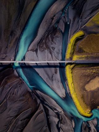An aerial view of the ground showing dark sand with a blue river cutting through it
