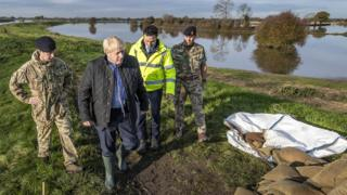 Boris Johnson walking along a flooded bank wearing wellies and surrounded by two soldiers