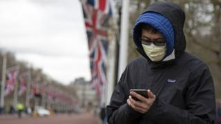 Man wearing a face mask in London with union flags draped on flagpoles in the background