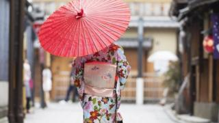 Japanese woman walking with traditional umbrella in Kyoto