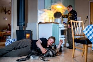 A young man strokes his dog as his father cooks behind him.