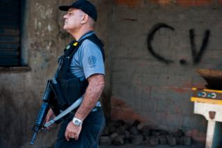 : A Brazilian military police patrol with the symbol at the bottom of the criminal group Comando Vermelho after entering the unspecified Complexo da Mare, one of the largest 'favela' complexes in Rio, on March 30, 2014 in Rio de Janeiro, Brazil.