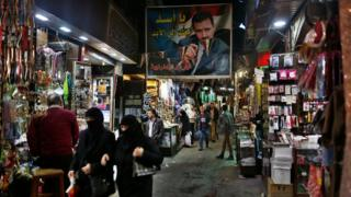 "A poster of the Syrian President Bashar Assad that reads ""Assad we are with you for ever"" in Arabic hangs at the popular Hamidiyeh old market in Damascus"