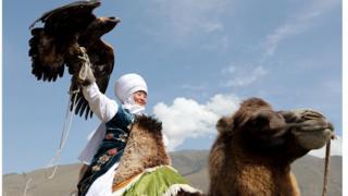 Участница соревнований по соколиной охоте верхом на верблюде