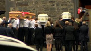 The coffins of the Hawe family are brought into the church