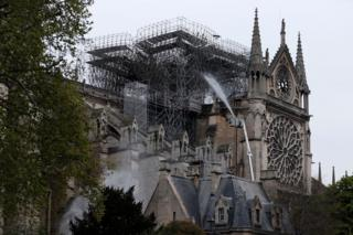 Firefighters spray water as they work to extinguish a fire at Notre-Dame Cathedral in Paris
