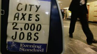 A city worker walks past an Evening Standard newspaper stand in Canary Wharf, London in 2008