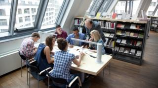 Professor auxilia alunos universitários em uma biblioteca