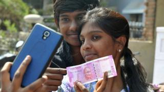 Indian customers pose for a 'selfie' with a new 2000INR currency note at a bank in Hyderabad on November 11, 2016.