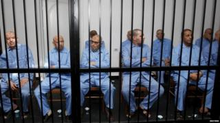 Former Gaddafi regime's officials sit behind bars during a verdict hearing at a courtroom in Tripoli, Libya July 28, 2015