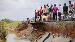 People gather on a destroyed section of road