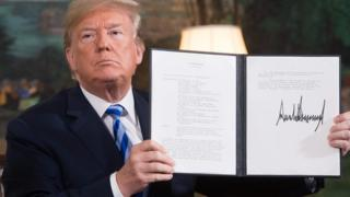 President Trump holds up a document related to the US withdrawal from Iran deal