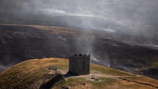 building on hill overlooking moorland