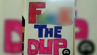 A placard that reads: Fuck the DUP